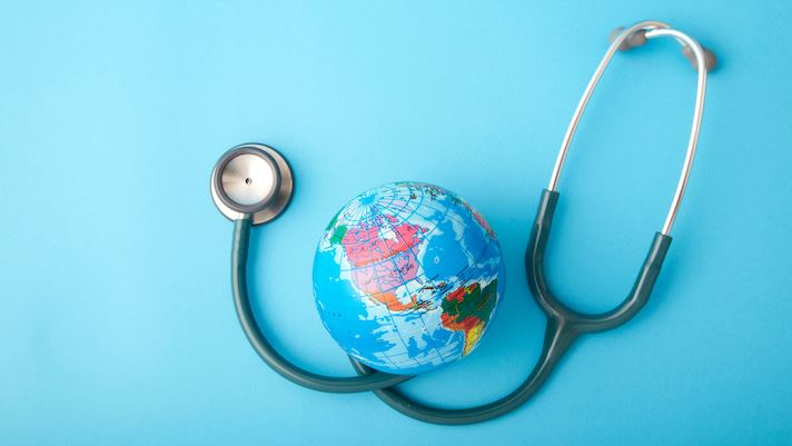 Blue background with stethoscope wrapped around small world globe